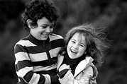 Brother and sister enjoy playing in the park, black and white image