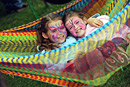 Two girls with their faces painted lie in a brightly coloured hammock