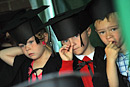 Three boys in mortar board hats take part in a play
