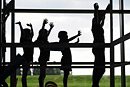 A silhouette of children on a climbing frame