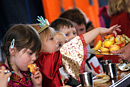 Children dressed for a school nativity play eat their lunch
