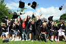 Children dressed as graduates throw their mortar boards in the air while cheering