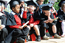 Children dressed as graduates play in the sunshine