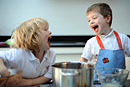 Two boys share a laugh while baking in the kitchen