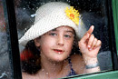 A girl chases raindrops on the window with her finger