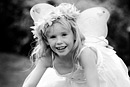 A girl plays dressed as an angel, black and white image