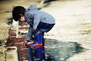 A toddler plays in a puddle in his wellington boots