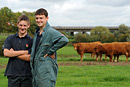 Two young farmers pose in fron of some cows