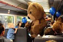 A boy meets a huge teddy bear on a train full of children