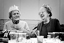 Two elderly ladies at a party share a laugh