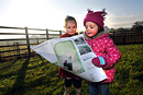 Two toddlers look at a map in a field on a cold winter morning