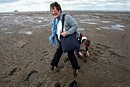 A grandmother and grandson get stuck in the wet sand on the beach