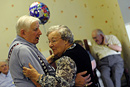 Two elderly residents enjoy a dance during a party
