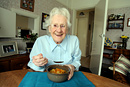 Portrait of an elderly woman enjoying her lunch provided by meals on wheels
