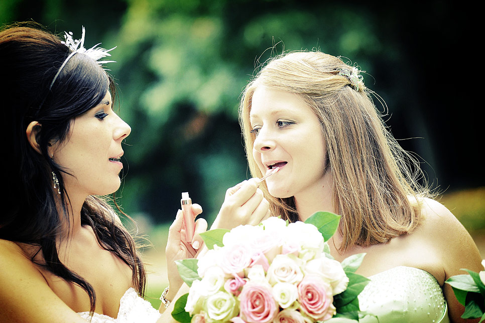 Bride adding lipgloss to the bridesmaid
